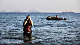 A Syrian migrant arrives after crossing from Turkey by a rubber boat, seen in the background, in the southeastern island of Kos, Greece, Monday, Aug. 17, 2015. Greek authorities said Sunday they have started resettling migrants living in tents in a park in the capital Athens   but many were wary and had moved out ahead of the operation. More than 130,000 migrants have reached Greece so far in 2015, straining the country's resources. (AP Photo/Alexander Zemlianichenko)
