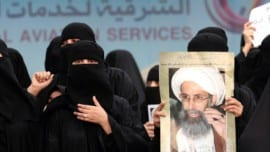 Saudi Shiite women hold placards bearing portraits of prominent Shiite Muslim cleric Nimr al-Nimr during a protest in the eastern coastal city of Qatif against his execution by Saudi authorities, on January 2, 2016. Nimr was a driving force of the protests that broke out in 2011 in the kingdom's east, an oil-rich region where the Shiite minority of an estimated two million people complains of marginalisation. AFP PHOTO / STR / AFP / STR        (Photo credit should read STR/AFP/Getty Images)