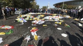 People surround the area where bodies of victims are covered with flags and banners at the site of an explosion in Ankara, Turkey, Saturday, Oct. 10, 2015. Two bomb explosions apparently targeting a peace rally in Turkey's capital Ankara on Saturday has killed over a dozen people, a news agency and witnesses said. The explosions occurred minutes apart near Ankara's train station as people gathered for the rally organized by the country's public sector workers' trade union. (AP Photo/Burhan Ozbilici)
