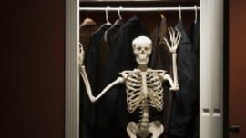 Skeleton standing in closet waving