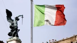 Tourists take in the view from the top of St Angelo's castle as an Italian national flag flies from a flagpole nearby in Rome, Italy, on Sunday, May 5, 2013. Italian banks' corporate loan book will worsen this year as the euro region's third-biggest economy remains mired in its longest recession in two decades, according to the nation's central bank. Photographer: Alessia Pierdomenico/Bloomberg